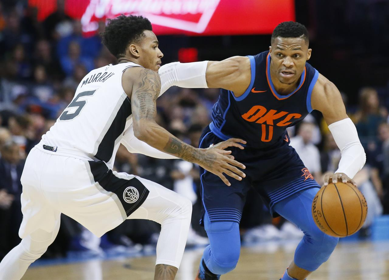 ea53b4406e9b Oklahoma City Thunder guard Russell Westbrook (0) drives around San Antonio  Spurs guard Dejounte Murray (5) during the first quarter of an NBA  basketball ...