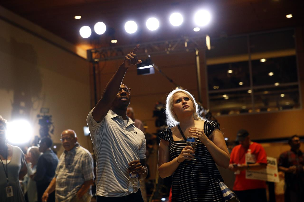 Dallas Matthews, left, and Tabitha Jackson, supporters of Maryland Democratic gubernatorial candidate Ben Jealous, watch voting results during an election night party, Tuesday, June 26, 2018, in Baltimore. Jealous and Prince George's County Executive Rushern Baker lead a crowded Democratic primary field to win a nomination to face popular Republican Gov. Larry Hogan in the fall. (AP Photo/Patrick Semansky)