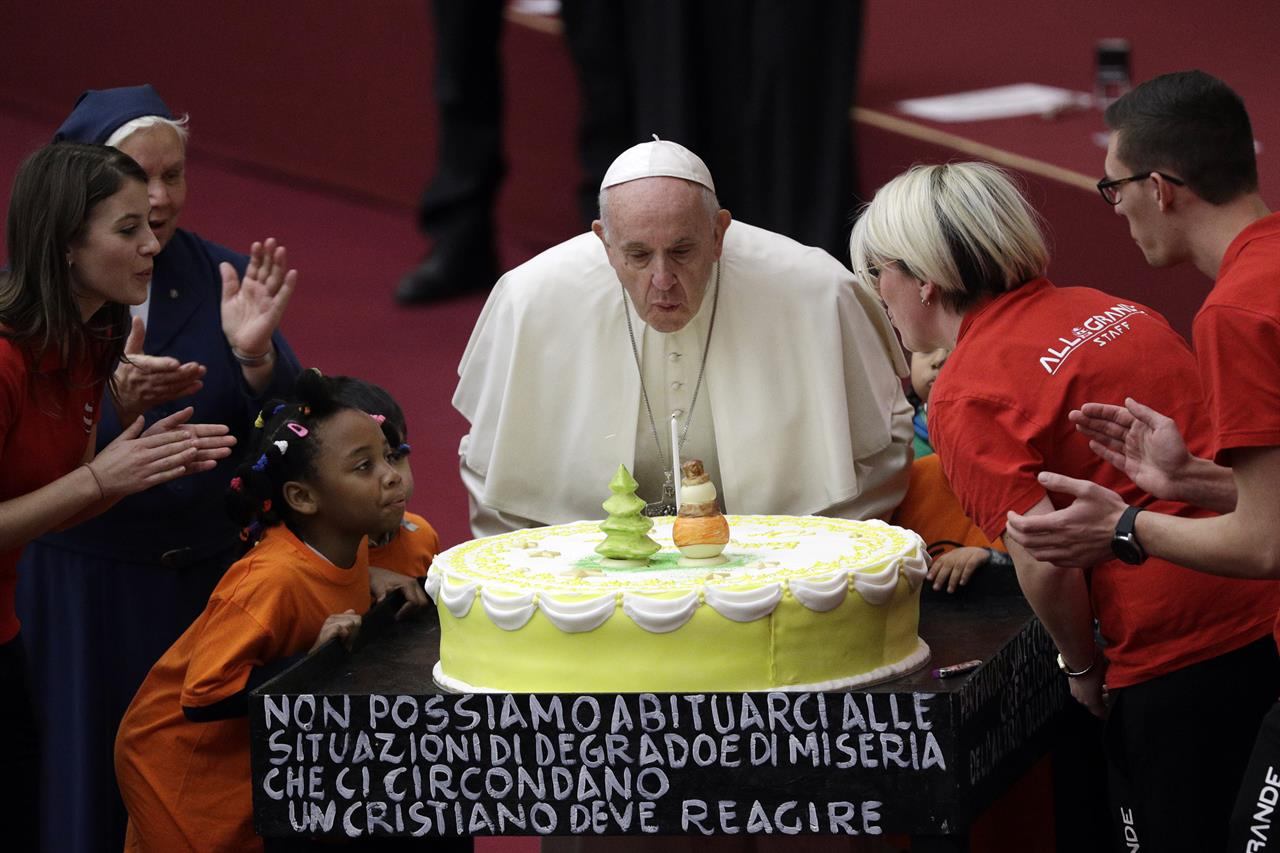 Pope Francis Blows A Candle Atop Of Cake He Was Offered On The Eve His 82nd Birthday During Audience With Children And Family From Dispensary