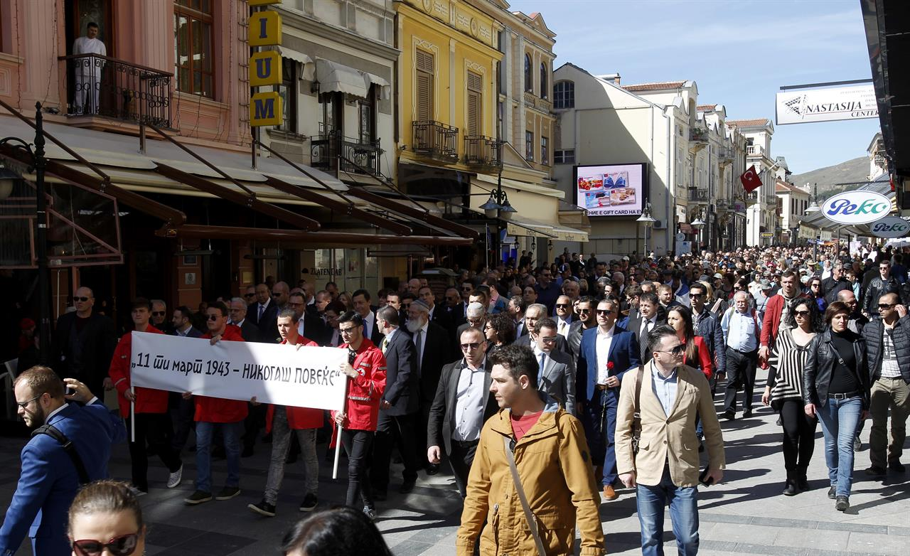 """People take part in the International March of the Living, through downtown Bitola, southern Macedonia, commemorating the victims of the Holocaust, on Sunday, March 11, 2018. Thousands of people have joined a march in southern Macedonian town of Bitola, commemorating 75 years of deportation and destruction of almost entire country's Jewish community in the Nazi extermination camp Treblinka, during World War II. The banner left reads in Macedonian """"11 of March 1943 - Never Again"""". (AP Photo/Boris Grdanoski)"""