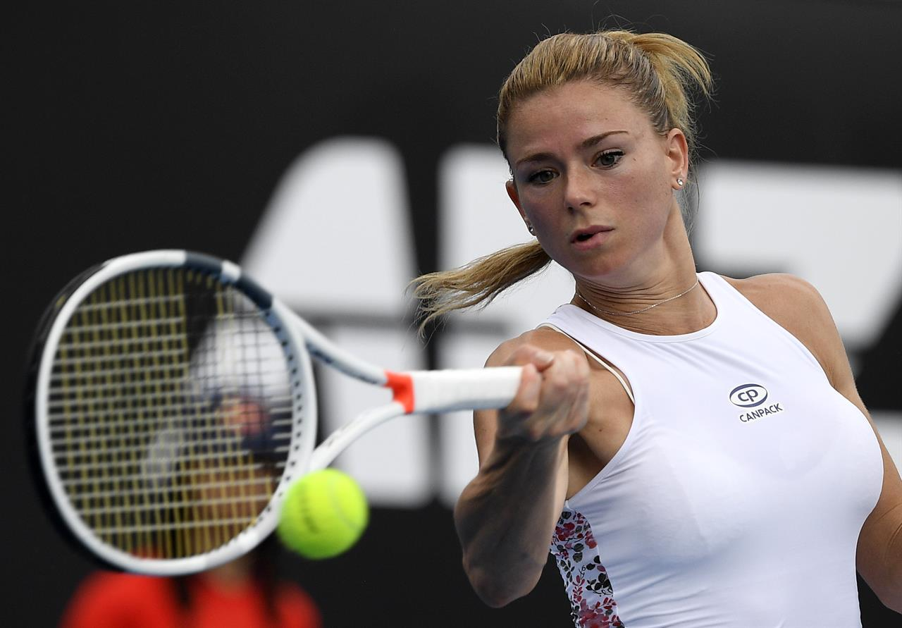 Italy s Camila Giorgi hits a forehand return to Poland s Iga Swiatek during  their second round match at the Australian Open tennis championships in ... 52c353dfe423