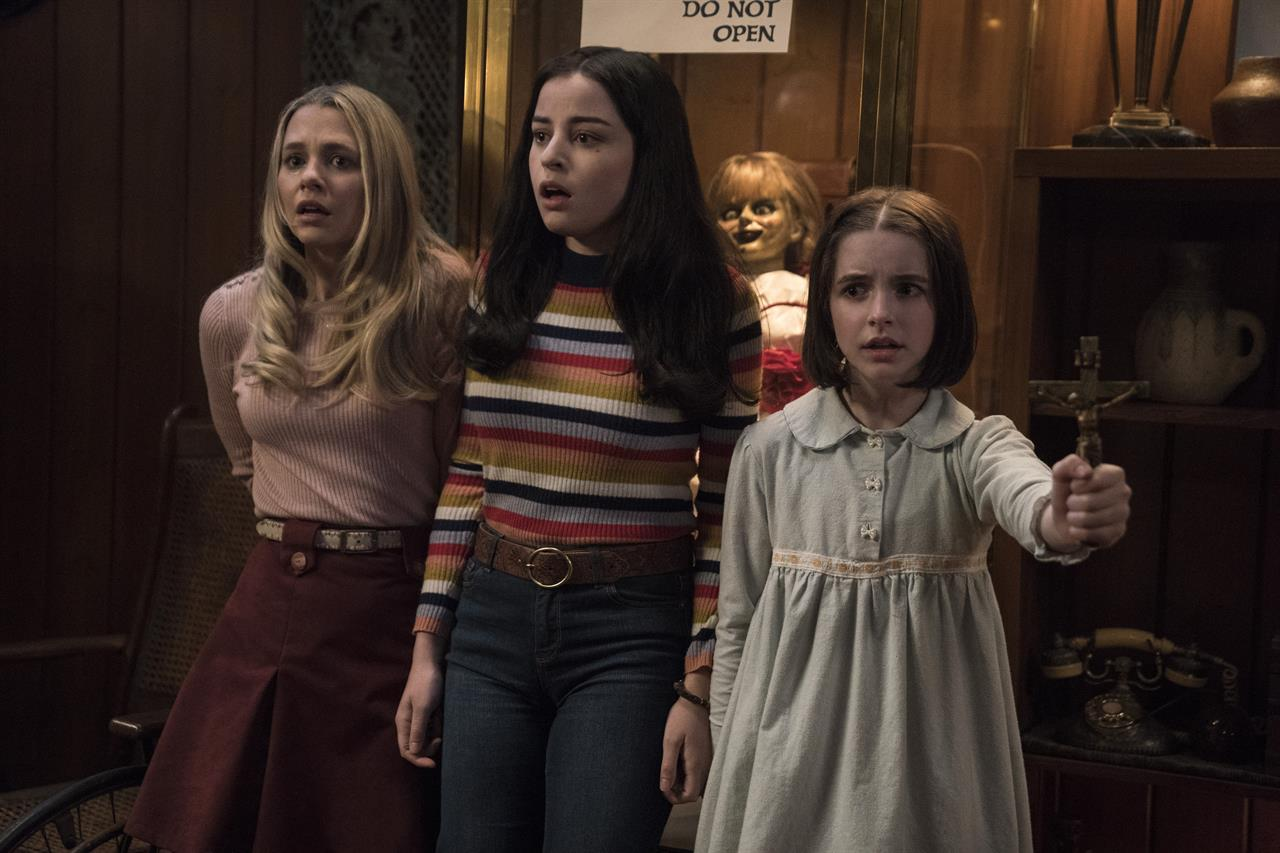 "This image released by Warner Bros. Pictures shows Madison Iseman, from left, Katie Sarife and McKenna Grace in a scene from the horror film, ""Annabelle Comes Home."" (Dan McFadden/Warner Bros. Pictures via AP)"