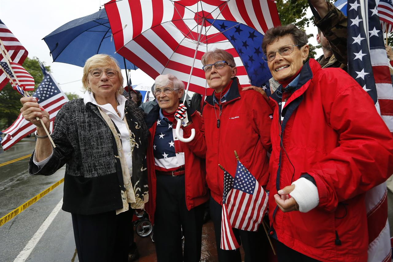 The Latest: 'Freeport flag ladies' wave flags one final time