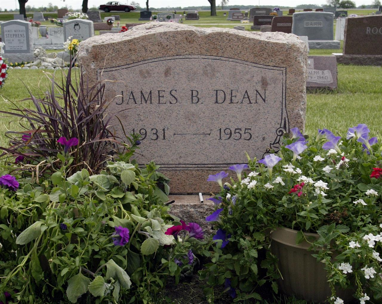 """FILE - This May 27, 2005 file photo shows plants and flowers at the grave of actor James Dean in Fairmount, Ind. Dean hasn't been alive in 64 years, but the """"Rebel Without a Cause"""" actor has been cast in a new film about the Vietnam War. The filmmakers behind the independent film """"Finding Jack"""" said Wednesday that a computer-generated Dean will play a co-starring role in the upcoming production. The digital Dean is to be assembled through old footage and photos and voiced by another actor. (AP Photo/John Harrell, File)"""