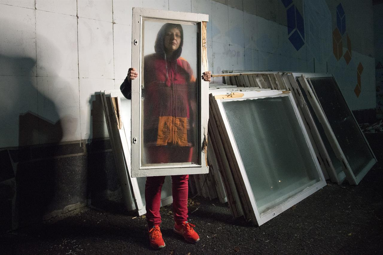 In this photo taken on Friday, Oct. 25, 2019, Olga, last name withheld for safety reasons, poses with a window frame in a park in Kyiv, Ukraine. After being snatched by pro-separatist militias from her hometown of Alchevsk in August 2014, Olga survived three mock executions and was rescued by her girlfriend 10 days later. (AP Photo/Zoya Shu)