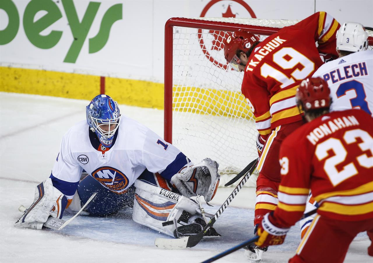480dc75b91d New York Islanders goalie Thomas Greiss, left, of Germany, stops a shot  from Calgary Flames' Matthew Tkachuk during the second period of an NHL  hockey game ...