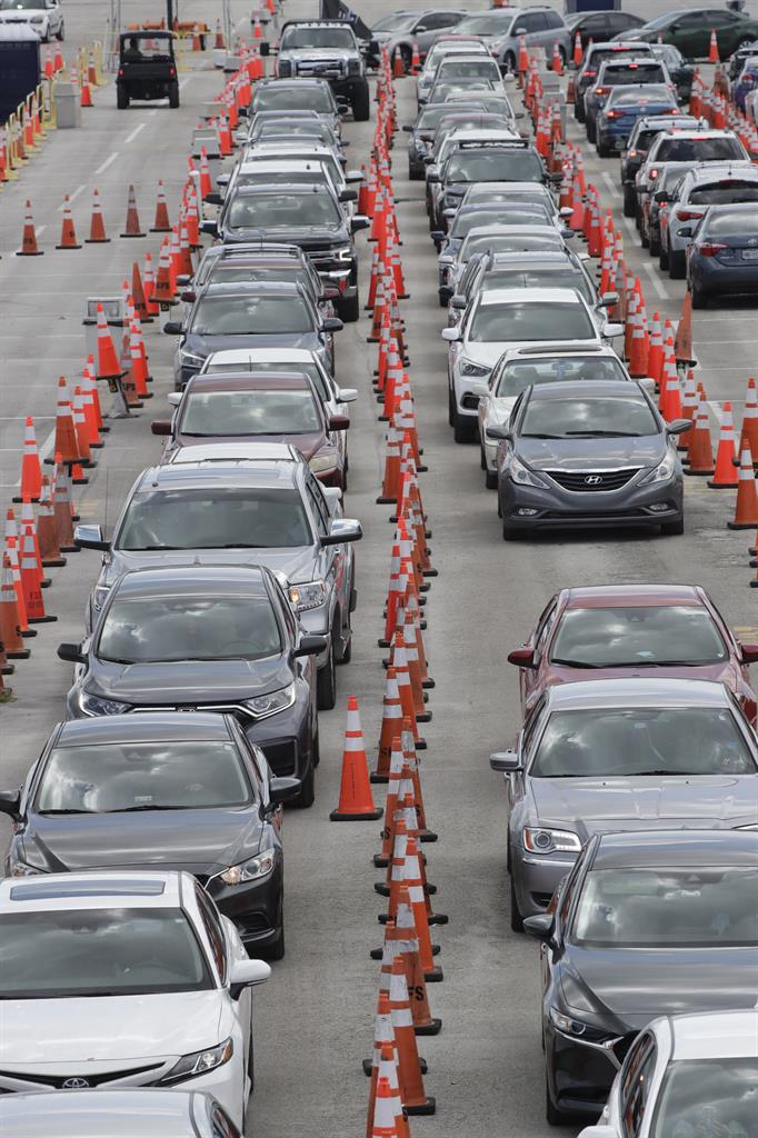 FILE - Cars wait in line at a drive-through COVID-19 testing site outside Hard Rock Stadium, in a Wednesday, July 8, 2020 file photo, in Miami Gardens, Fla. Florida on Sunday, July 13, 2020 reported the largest single-day increase in positive coronavirus cases in any one state since the beginning of the pandemic. (AP Photo/Wilfredo Lee)