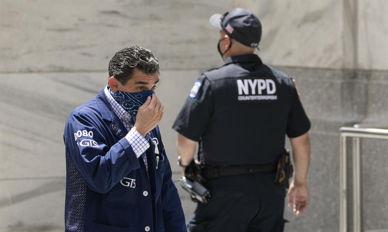 A stock trader, left, adjusts his mask as he enters the New York Stock Exchange, Thursday, July 30, 2020.  Strong gains for Big Tech stocks are helping to prop up Wall Street in early Friday trading following blowout profit reports from some of the market's most influential companies.  (AP Photo/Mark Lennihan)