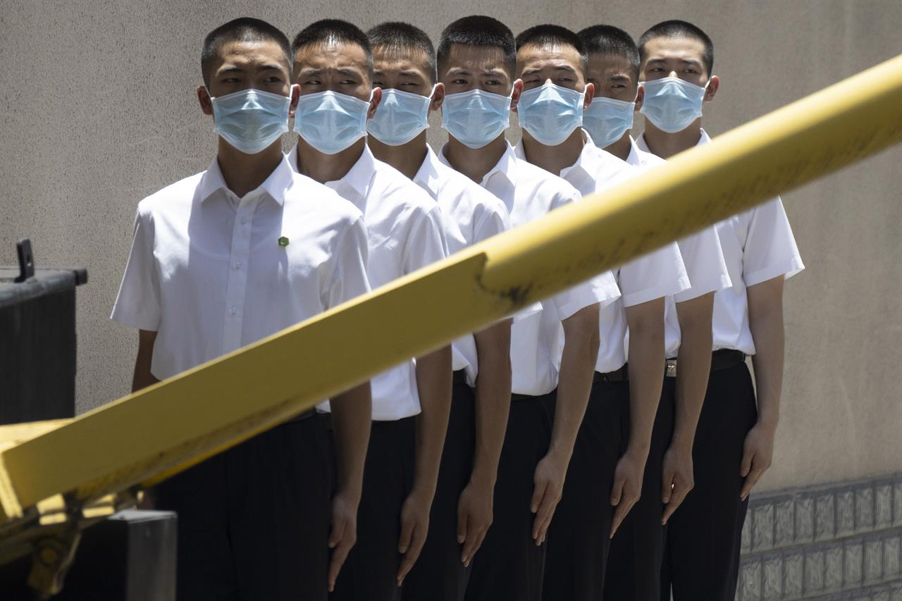 Security personnel wearing face masks line up outside the former United States Consulate in Chengdu in southwest China's Sichuan province on Monday, July 27, 2020. Chinese authorities took control of the former U.S. consulate in the southwestern Chinese city of Chengdu on Monday after it was ordered closed in retaliation for a U.S. order to vacate the Chinese Consulate in Houston. (AP Photo/Ng Han Guan)