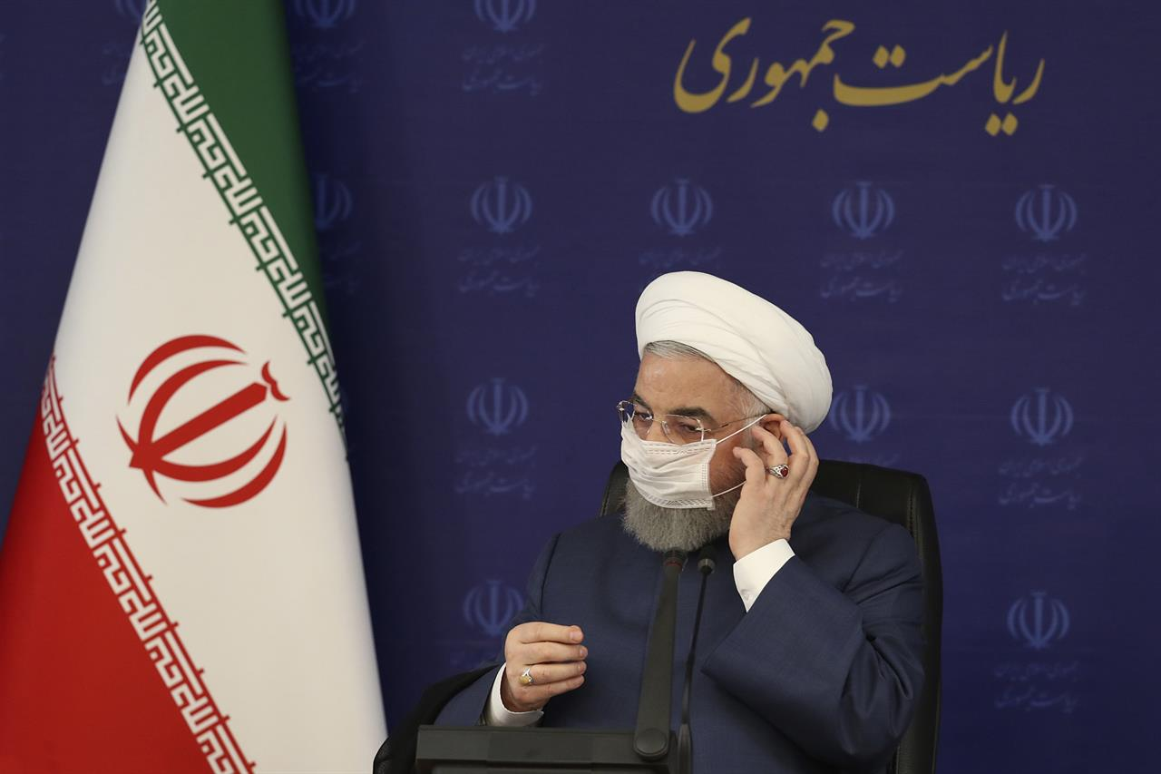 """FILE - In this July 18, 2020 file photo, released by the official website of the office of the Iranian Presidency, President Hassan Rouhani adjusts his face mask in a meeting of the national headquarters of the fight against the COVID-19, in Tehran, Iran. Iranian hard-liners in parliament voted Wednesday, Aug. 12, 2020, against Rouhani's nominee for trade minister. The vote marked the first serious confrontation between the newly elected house, dominated by conservatives and the bloc of supporters of the relatively moderate Rouhani. Writing in Farsi reads: """"The Presidency."""" (Iranian Presidency Office via AP, File)"""