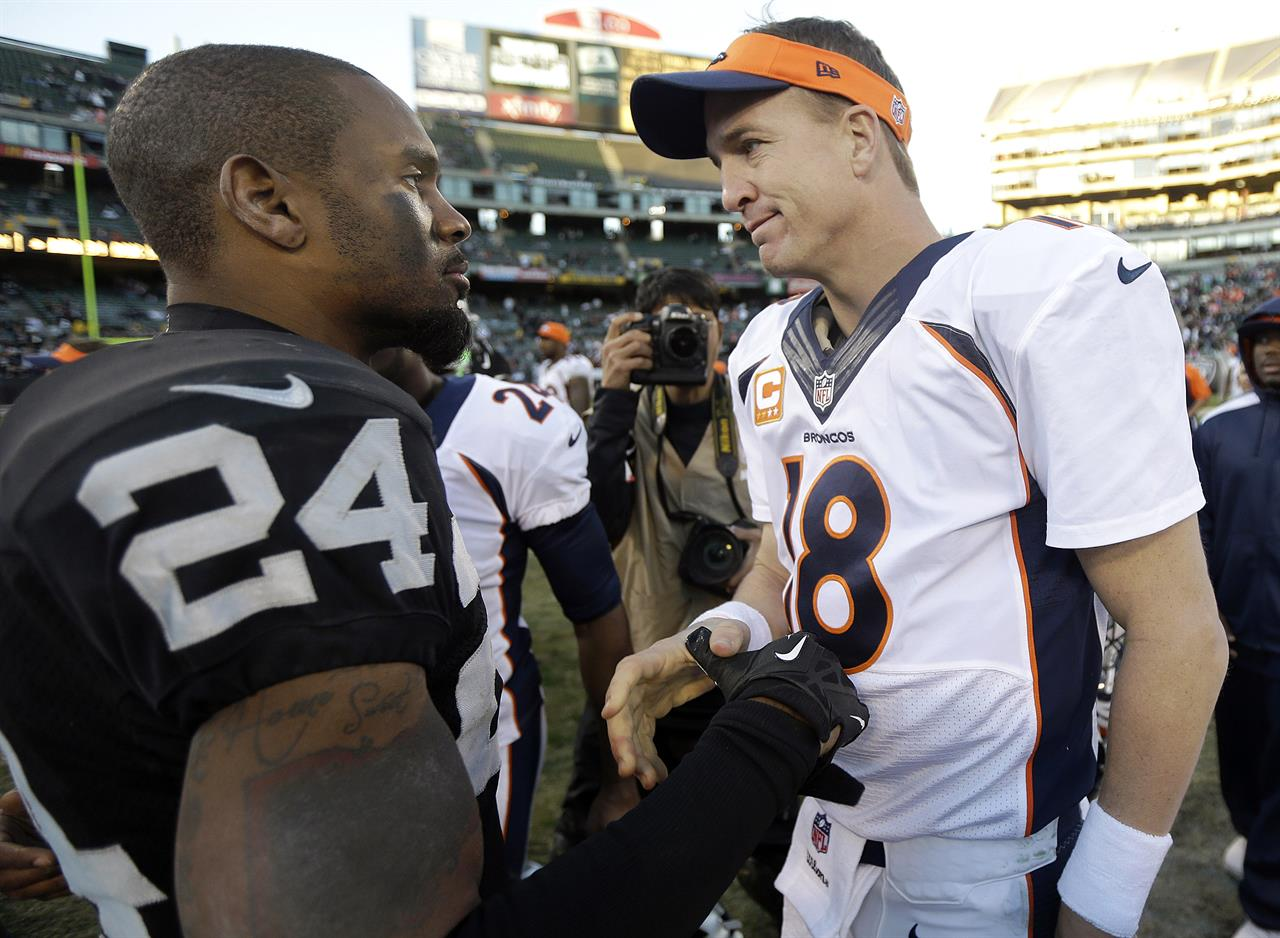 FILE - In this Dec. 29, 2013, file photo, Oakland Raiders cornerback Charles Woodson (24) talks with Denver Broncos quarterback Peyton Manning (18) after an NFL football game in Oakland, Calif. Peyton Manning and Charles Woodson are among 14 first-year eligible candidates for the Pro Football Hall of Fame. (AP Photo/Marcio Jose Sanchez, File)