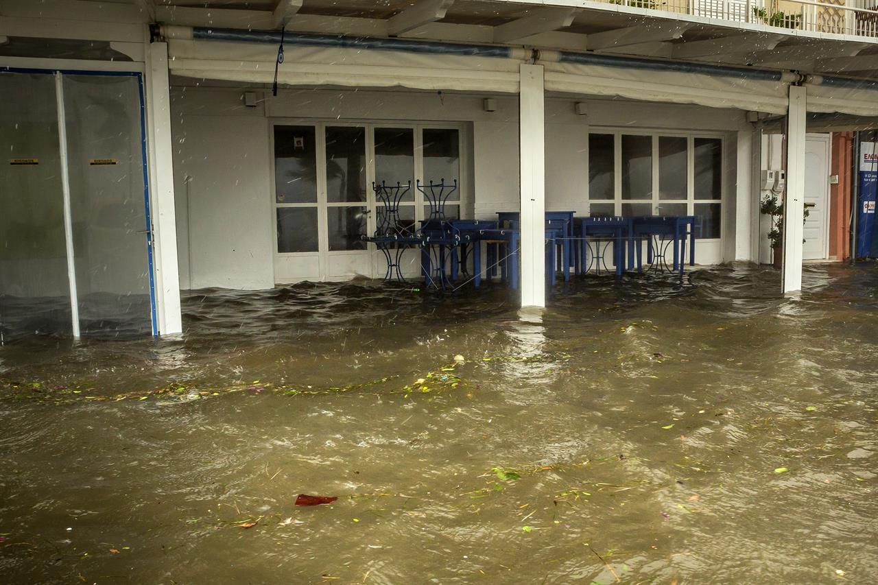 Seawater from crashing waves cover the yard of a tavern during a storm at the port of Argostoli, on the Ionian island of Kefalonia, western Greece, Friday, Sept. 18, 2020. Hurricane-force winds and heavy rainfall battered several islands off the western coast of Greece Friday, causing power outages and road closures, as authorities in nearby mainland areas remained on alert. (AP Photo/Nikiforos Stamenis)