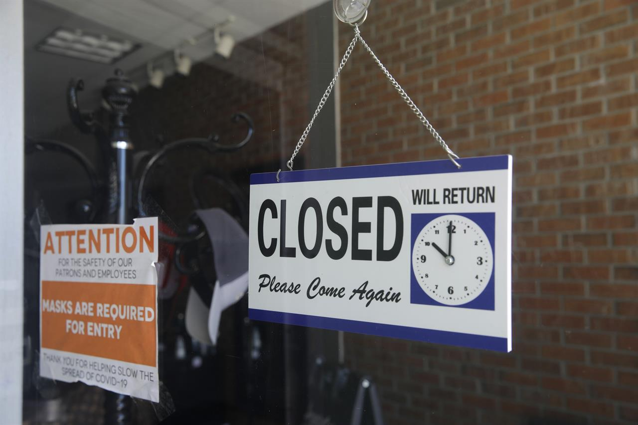 FILE - In this July 18, 2020 file photo a closed sign hangs in the window of a barber shop in Burbank, Calif. California's unemployment rate has fallen to 11.4% in August. The Employment Development Department says the state added 101,900 jobs in August. Most of those were government jobs, including temporary positions for the U.S. Census. California lost more than 2.6 million jobs in March and April because of the coronavirus. (AP Photo/Marcio Jose Sanchez, File)