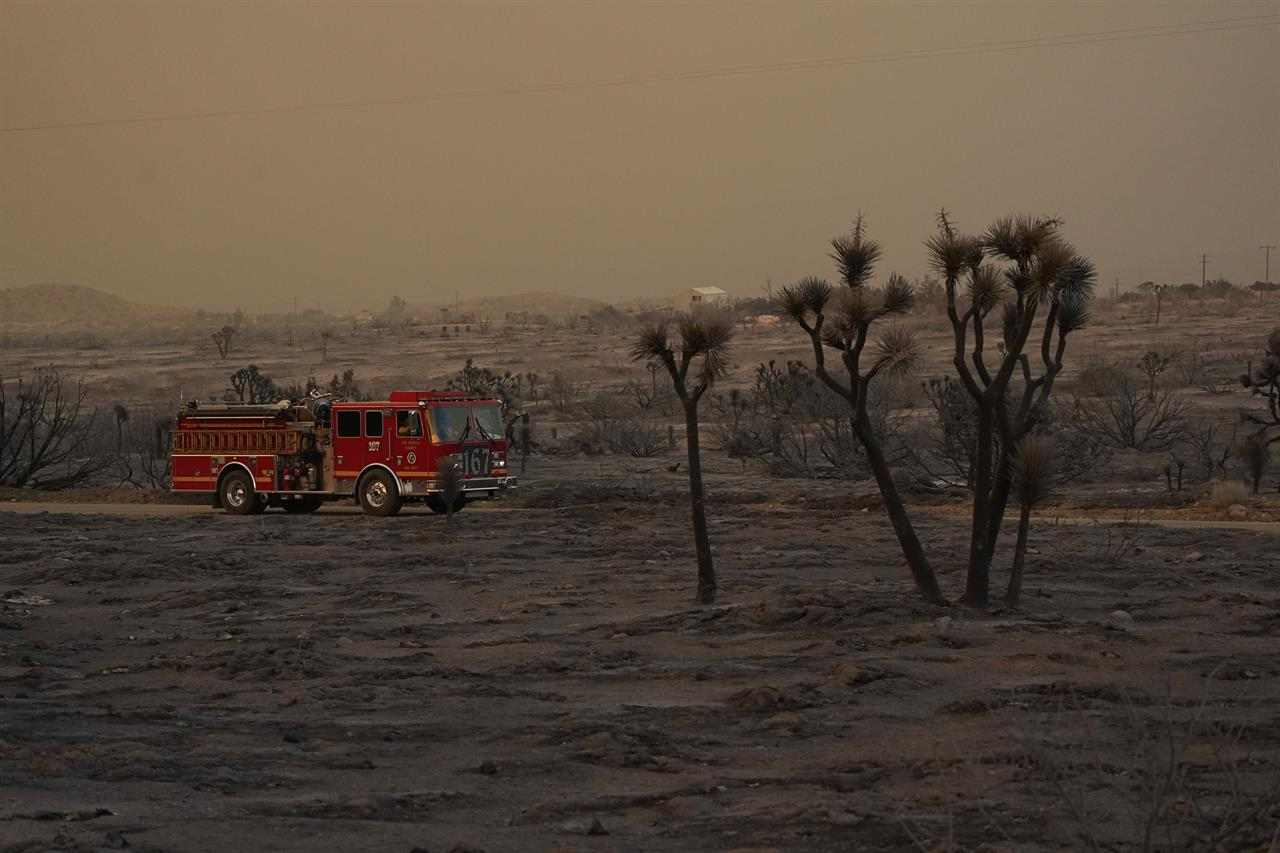 A fire engine is driven through the devastation left behind by the Bobcat Fire on Saturday, Sept. 19, 2020, in Juniper Hills, Calif. (AP Photo/Marcio Jose Sanchez)