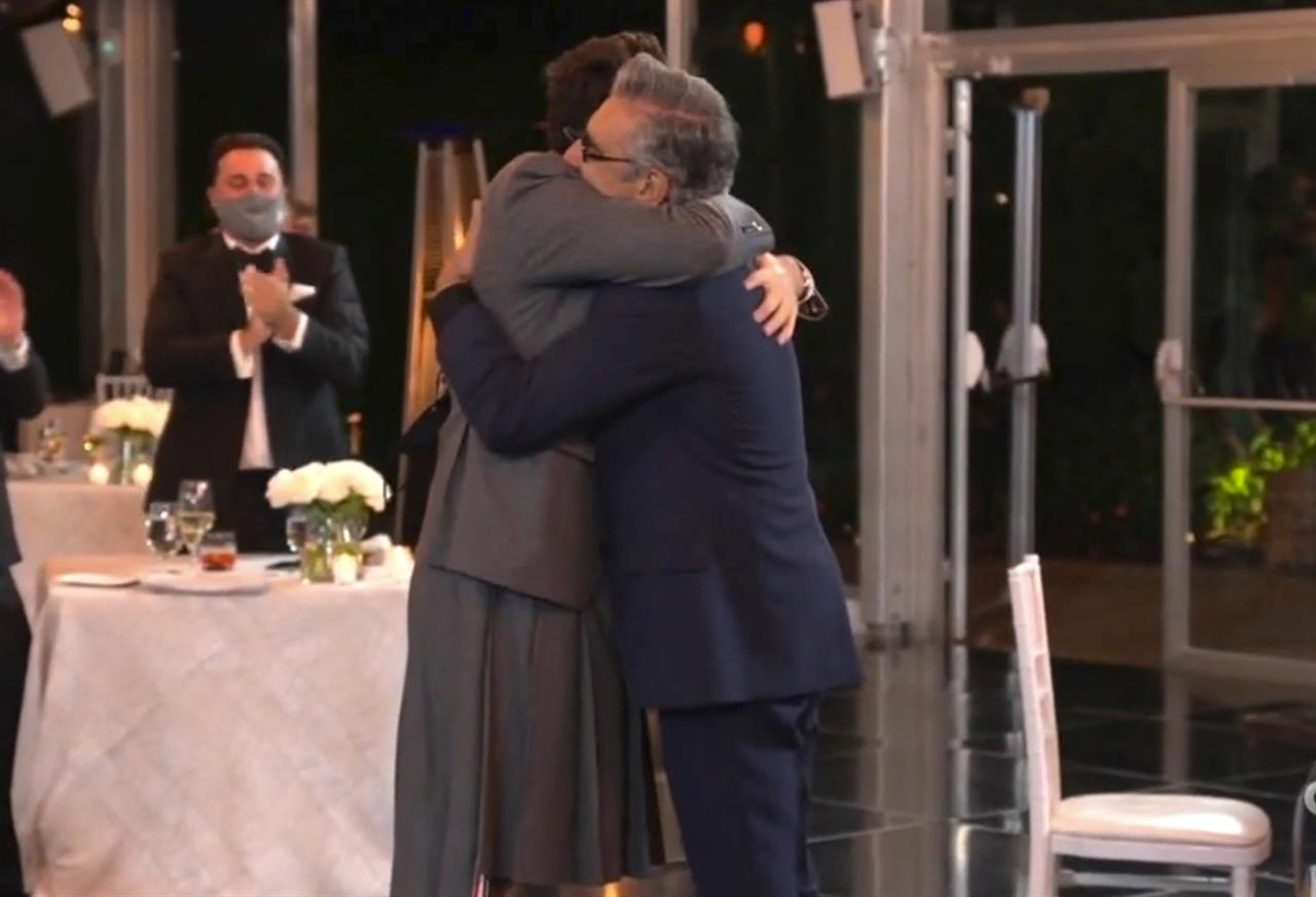 """In this video grab captured on Sept. 20, 2020, courtesy of the Academy of Television Arts & Sciences and ABC Entertainment, Dan Levy, left, hugs his father Eugene Levy, winner of the award for outstanding lead actor in a comedy series for """"Schitt's Creek"""" during the 72nd Emmy Awards broadcast. (The Television Academy and ABC Entertainment via AP)"""