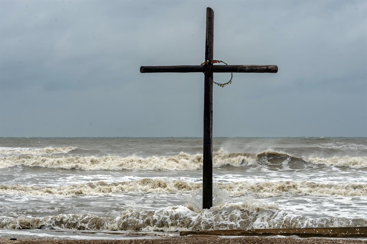 The cross that stands on the beach near the intersection of Highway 124 and Highway 87 gets buffeted by the high seas on Bolivar Peninsula, Texas, Sunday, Sept. 20, 2020. Tropical Storm Beta was expected this week to bring heavy rainfall to parts of the upper Texas Gulf Coast and Louisiana, adding to the stress and worry residents and officials have already dealt with during a busy hurricane season. (Fran Ruchalski/The Beaumont Enterprise via AP)