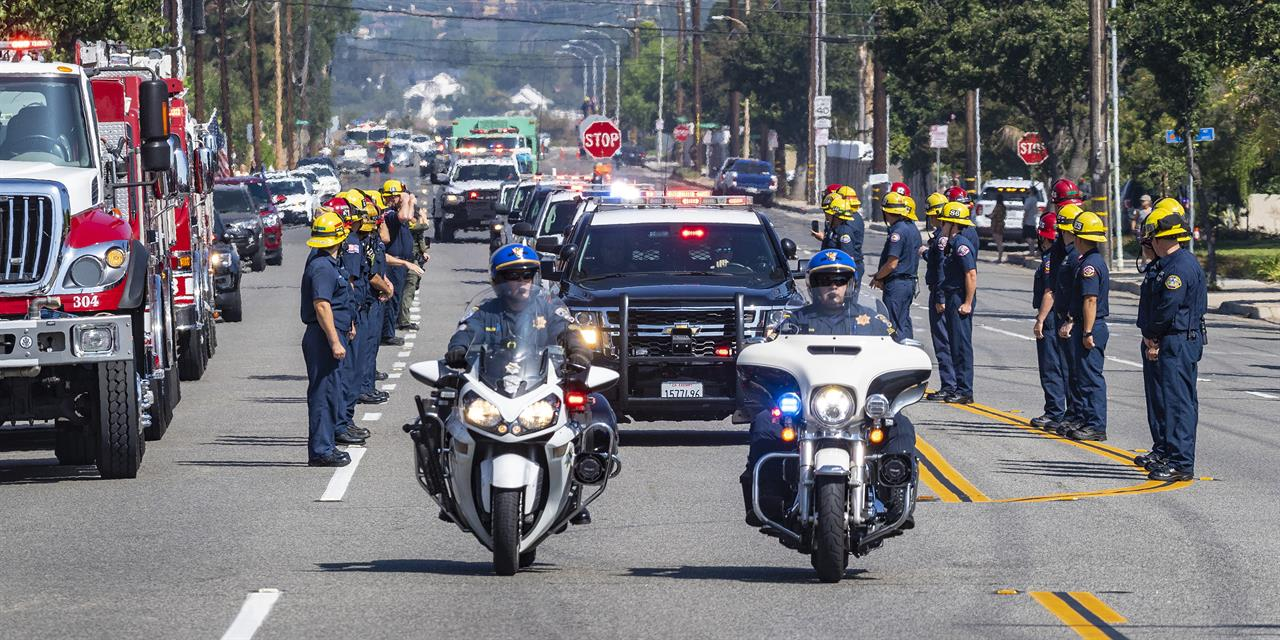 The California Highway Patrol leads the procession along with U.S. Forest Service vehicles as they escort fallen firefighter Charles Morton, killed while battling a blaze in the mountains east of Los Angeles, along Hewes Street in Orange, Calif., Tuesday, Sept. 22, 2020, from San Bernardino to the Ferrara Colonial Mortuary in Orange. Morton, 39, a San Diego native, was a 14-year veteran of the U.S. Forest Service and a squad boss for the Big Bear Interagency Hotshots in San Bernardino National Forest, officials said.  (Mark Rightmire/The Orange County Register via AP)