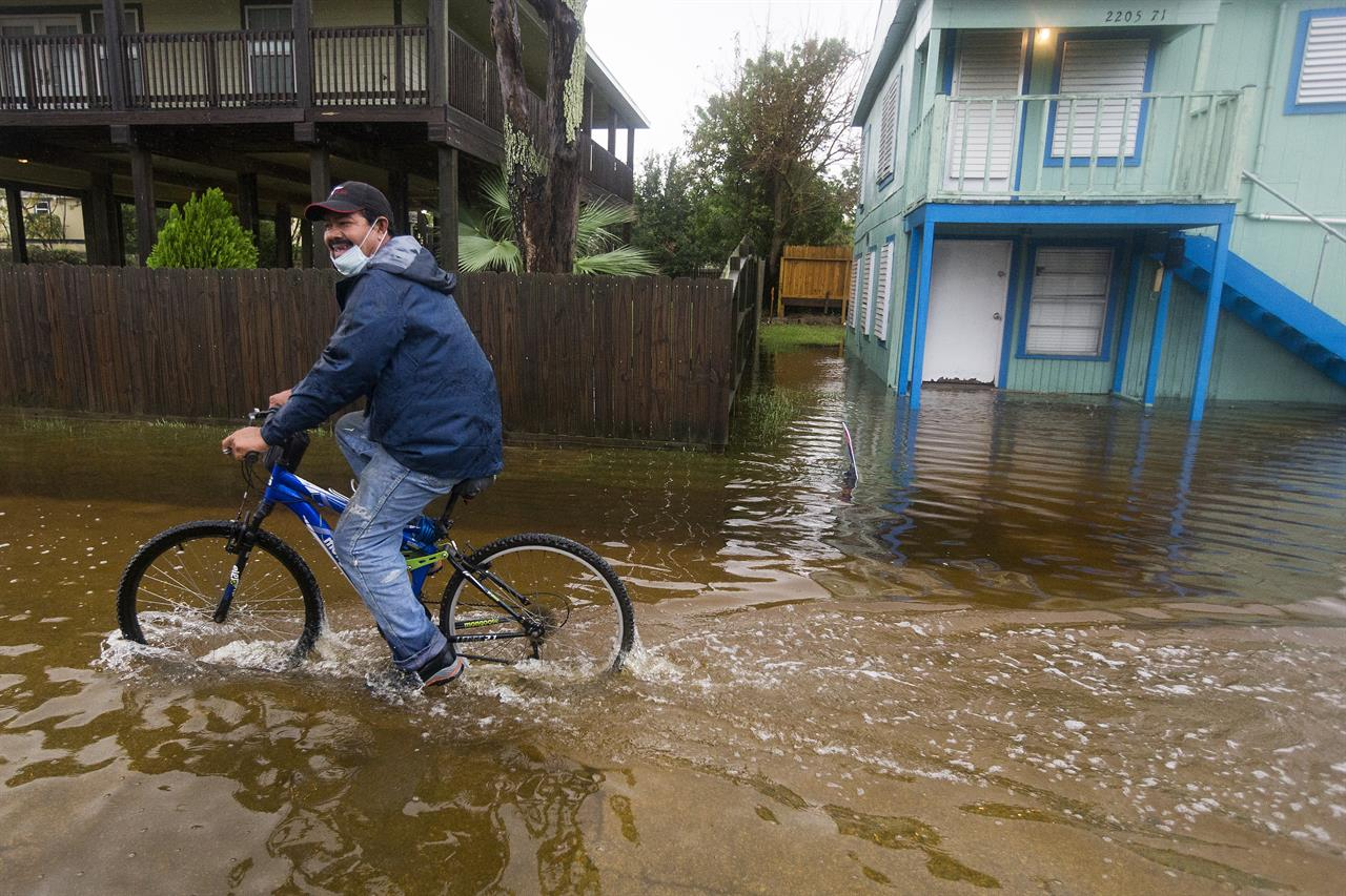 Rafael Juarez rides his bicycle through a street flooded by Tropical Storm Beta as he makes his way home from the store Monday, Sept. 21, 2020, in Galveston, Texas. (Brett Coomer/Houston Chronicle via AP)