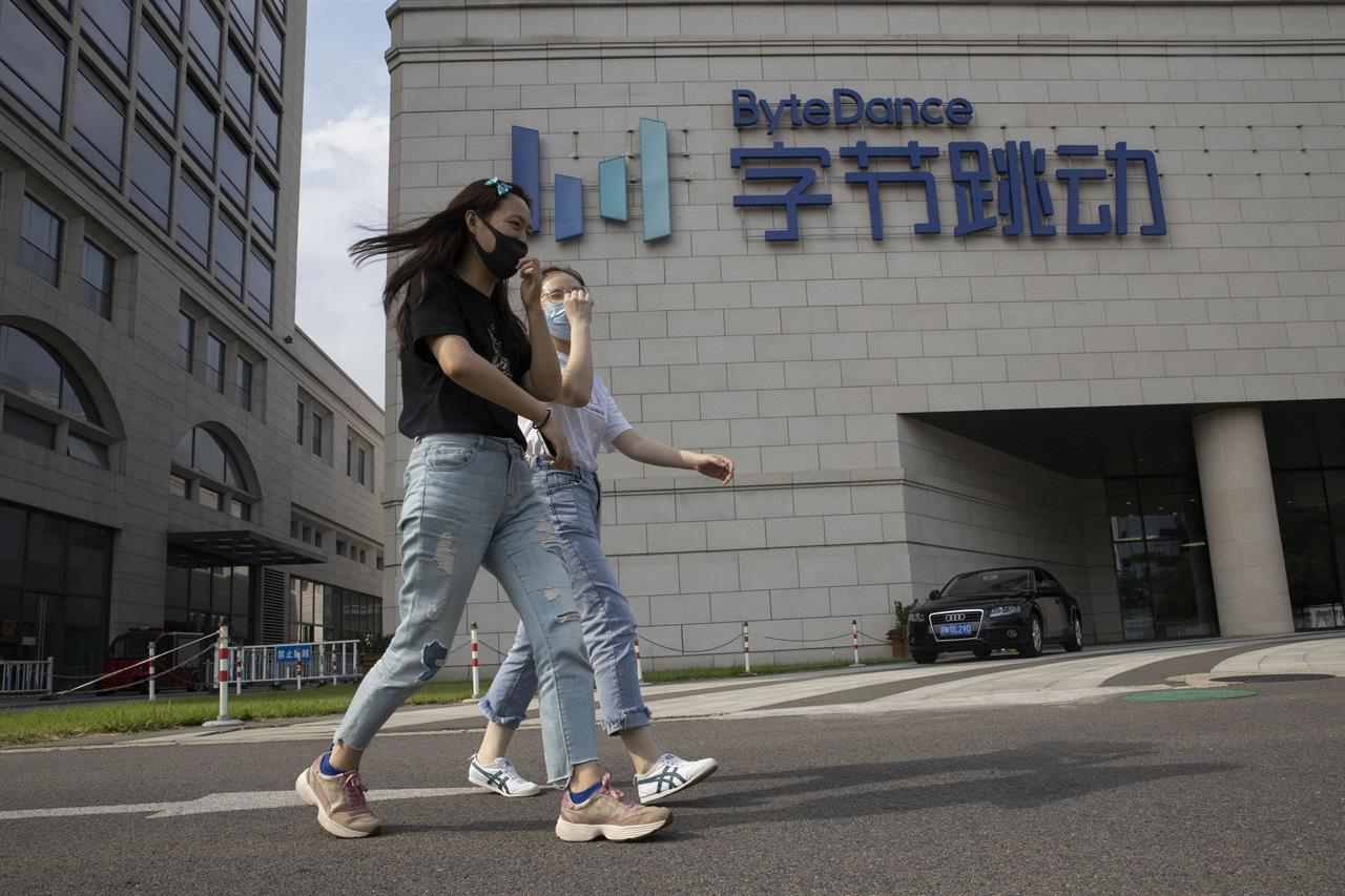 FILE - In this Aug. 7, 2020, file photo, women wearing masks to prevent the spread of the coronavirus chat as they pass by the headquarters of ByteDance, owners of TikTok, in Beijing, China. TikTok's owner said Thursday, Sept. 24, 2020, that it has applied for a Chinese technology export license as it tries to complete a deal with Oracle and Walmart to keep the popular video app operating in the United States. (AP Photo/Ng Han Guan, File)