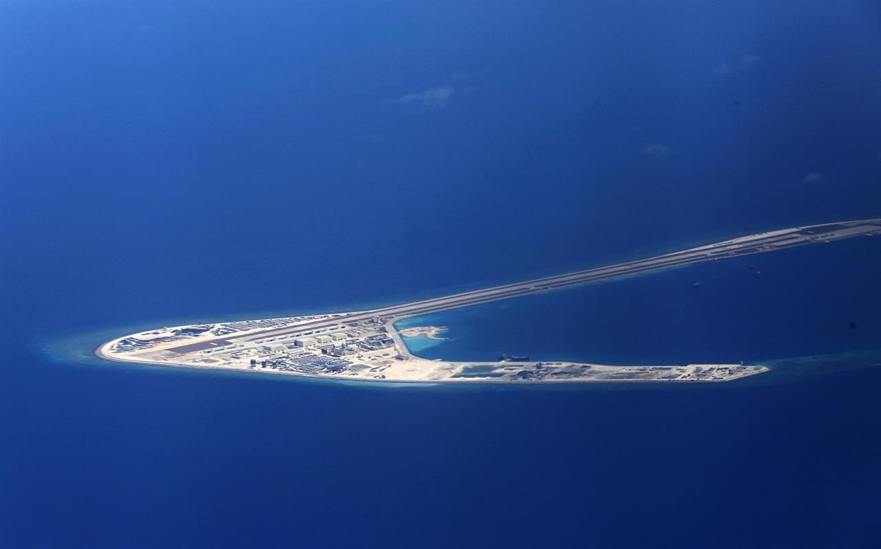 FILE - In this April 21, 2017, file photo, Chinese structures and an airstrip on the man-made Subi Reef at the Spratlys group of islands are seen from a Philippine Air Force C-130 transport plane off the disputed South China Sea in western Philippines. U.S.-China friction has flared again, with Beijing firing back at accusations by Washington that it is a leading cause of global environmental damage and has reneged on its promise not to militarize the South China Sea. (Francis Malasig/Pool Photo via AP, File)