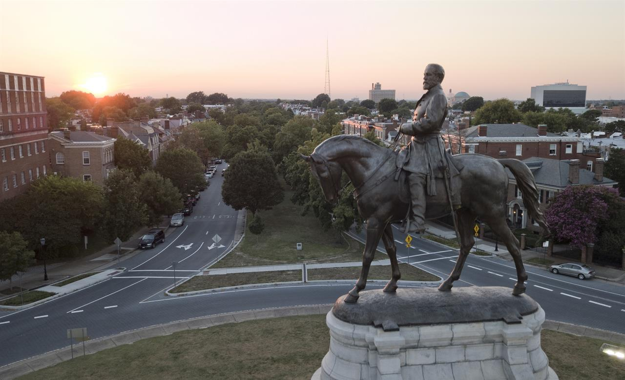 FILE - In this July 31, 2017, file photo, the sun sets behind the statue of Confederate Gen. Robert E. Lee on Monument Avenue in Richmond, Va. In a state where Confederate monuments have stood for more than a century and have recently become a flashpoint in the national debate over racial injustice, Virginians remain about evenly divided on whether the statues should stay or go, according to a new poll. The poll conducted this month by Hampton University and The Associated Press-NORC Center for Public Affairs Research found that 46% support removal of Confederate statues and 42% oppose removal. (AP Photo/Steve Helber, File)