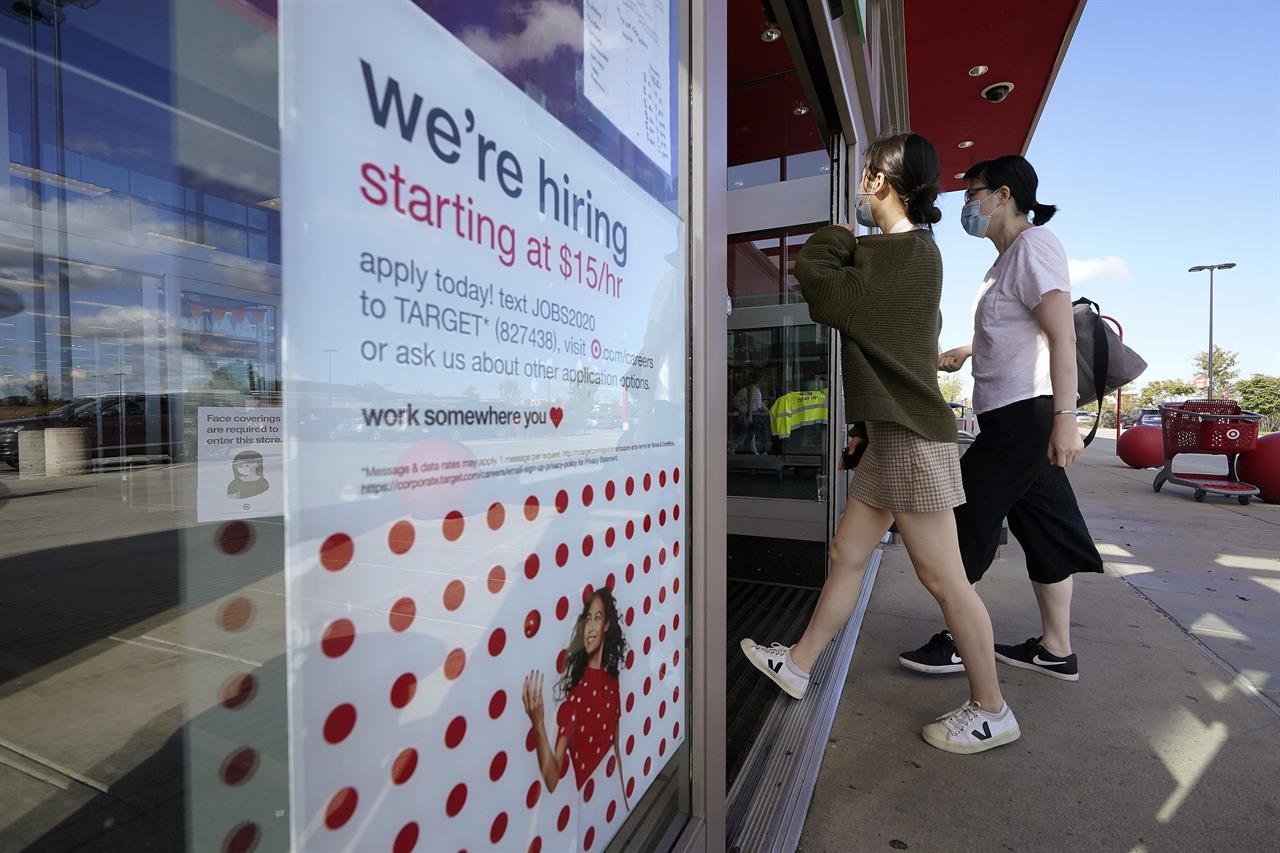 Passers-by walk past a hiring sign as they enter a Target retail store location, Wednesday, Sept. 30, 2020, in Westwood, Mass. The number of Americans seeking unemployment benefits declined last week to a still-high 837,000, evidence that the economy is struggling to sustain a tentative recovery that began this summer.  (AP Photo/Steven Senne)