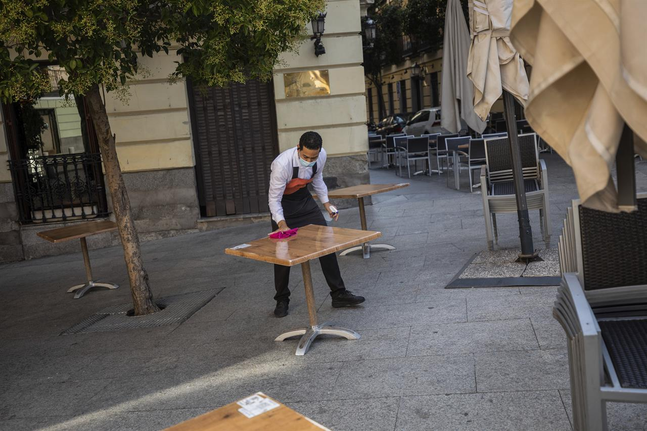 Waiter Miguel Santana disinfects a table prior opening a bar terrace in downtown Madrid, Spain, Wednesday, Sept. 30, 2020. The Spanish capital and its suburbs, the region in Europe where a second coronavirus wave is expanding by far the fastest, are edging closer to stricter mobility curbs and limits on social gatherings after days of a political row that has angered many Spaniards. (AP Photo/Bernat Armangue)