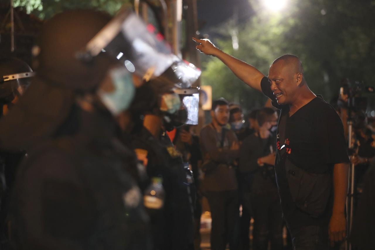 A pro-democracy protester shouts at Thai policemen during a demonstration in Bangkok, Thailand, Thursday, Oct. 15, 2020. Thai police dispersed a group of protesters holding an overnight rally outside the prime minister's office. (AP Photo/Rapeephat Sitichailapa)