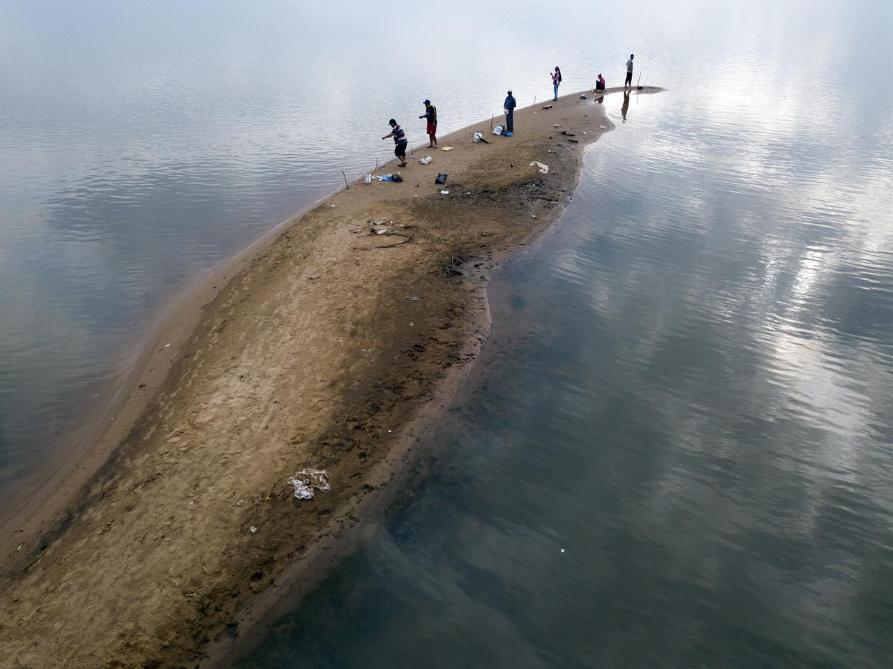 Men fish from a sand bank on the Paraguay River, taking advantage of the historical drop of water levels in San Antonio, Paraguay, on the outskirts of Asuncion, on Thursday, Oct. 15, 2020. (Ap Photo/Jorge Saenz)