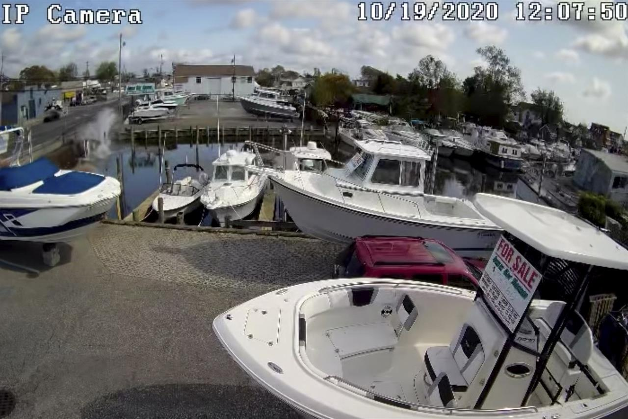 In this Oct. 19, 2020 image taken from surveillance video provided by Great Bay Marine via Suffolk County Police Department, a vehicle at the top left plunges into a canal in Lindenhurst, N.Y. Bystanders jumped into the water to rescue an elderly couple from a sinking car Monday after it careened into the canal on New York's Long Island. Police said that the couple were taken to a hospital for treatment of non-life-threatening injuries. (Great Bay Marine via Suffolk County Police Department via AP)
