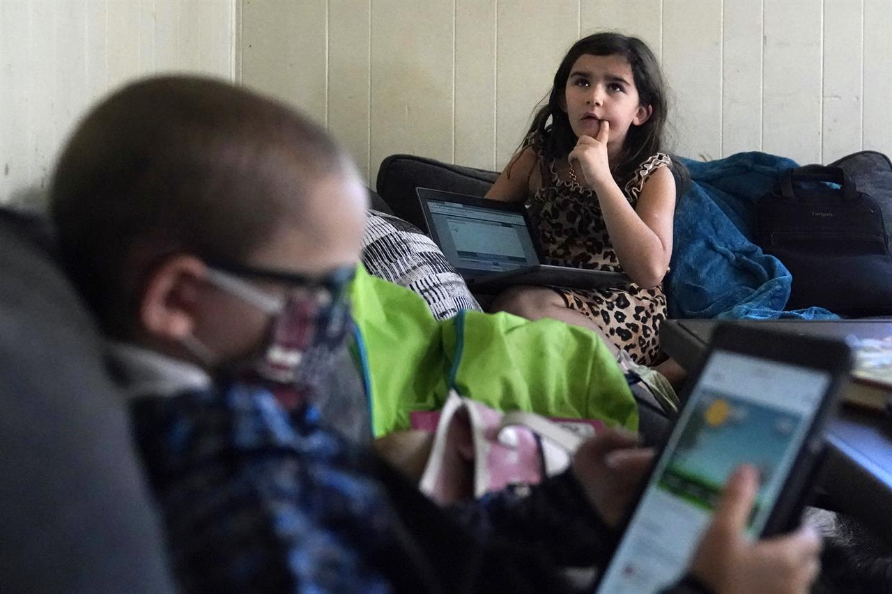 Third grade student Elena thinks while reciting multiplication tables, as her brother Wyatt reviews his kindergarten work on a tablet with their mom, Christi Brouder, in the living room of the family home, while remote learning due to the COVID-19 outbreak, Wednesday, Oct. 14, 2020, in Haverhill, Mass. The Brouder family has four children that are distance learning. Many families with multiple students, some with special needs, are dealing with the challenges of remote distance learning in their home. (AP Photo/Charles Krupa)