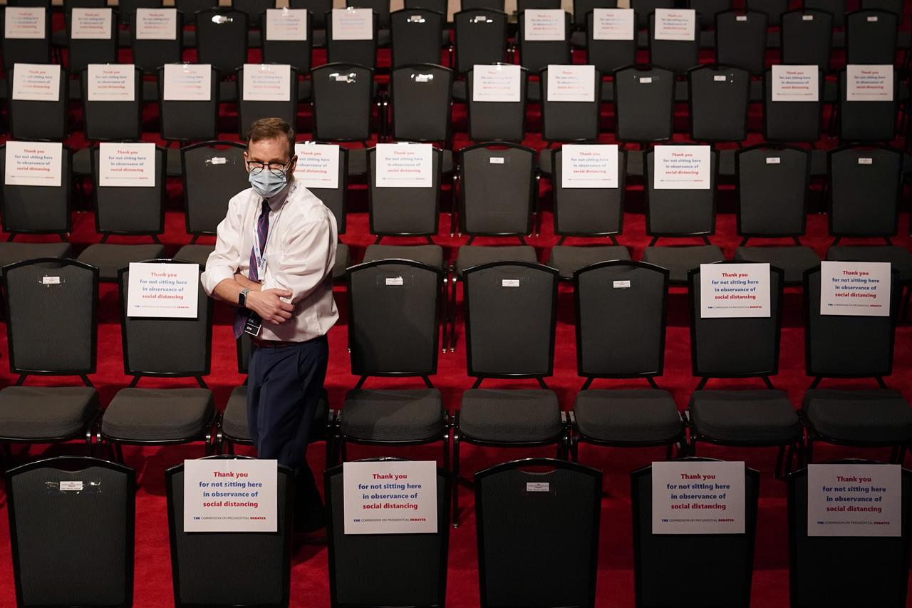 An official walks past spectator seating marked with signs observing social distancing requirments as preparations take place for the second Presidential debate between President Donald Trump and Democratic presidential candidate, former Vice President Joe Biden at Belmont University, Thursday, Oct. 22, 2020, in Nashville, Tenn. (AP Photo/Patrick Semansky)