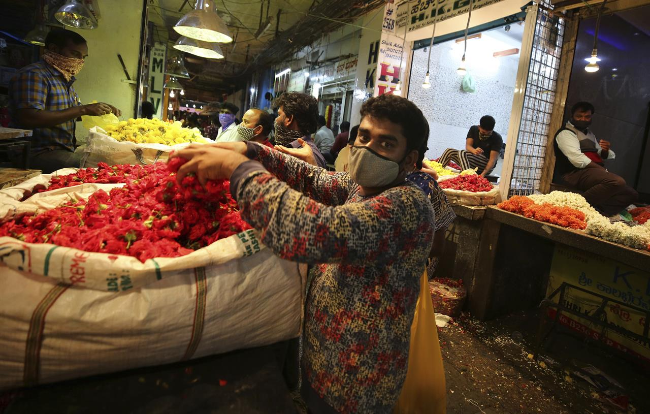 Vendors arrange flowers at a wholesale flower market ahead of the Hindu festival of Dussehra, in Bengaluru, India, Friday, Oct. 23, 2020. Health officials have warned about the potential for the coronavirus to spread during the upcoming religious festival season, which is marked by huge gatherings in temples and shopping districts. (AP Photo/Aijaz Rahi)