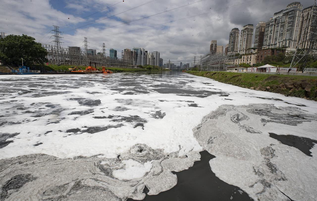 Foam blankets a portion of the Pinheiros River in Sao Paulo, Brazil, Thursday, Oct. 22, 2020. Affected by domestic sewage and solid wastes discharges for years, Sao Paulo's state government is again trying to clean the Pinheiros River, considered one of the most polluted in Brazil. (AP Photo/Andre Penner)