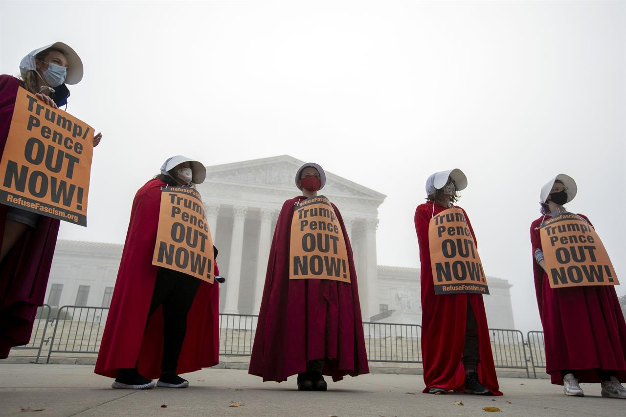 "Activists opposed to the confirmation of President Donald Trump's Supreme Court nominee, Judge Amy Coney Barrett, dressed as characters from ""The Handmaid's Tale,"" protest at the Supreme Court on a foggy day, Thursday, Oct. 22, 2020 in Washington. (AP Photo/Jose Luis Magana)"