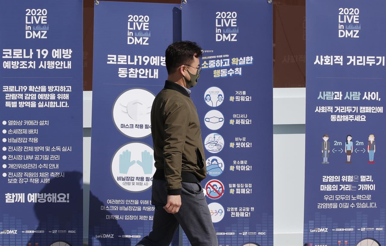 A man wearing a face mask walks past near banners showing precaution against the coronavirus, at the Imjingak Pavilion in Paju, South Korea, Friday, Oct. 23, 2020. South Korea recorded its highest increase in coronavirus cases in more than 40 days on Friday as more infections were reported at hospitals and nursing homes. (AP Photo/Lee Jin-man)