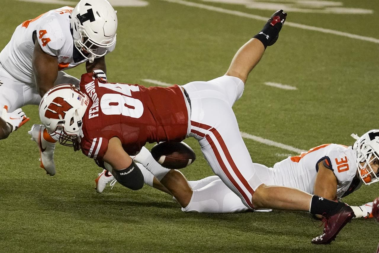 Wisconsin's Jake Ferguson fumbles the ball during the first half of an NCAA college football game against Illinois Friday, Oct. 23, 2020, in Madison, Wis. Illinois recovered the fumble and scored a touchdown on the play. (AP Photo/Morry Gash)