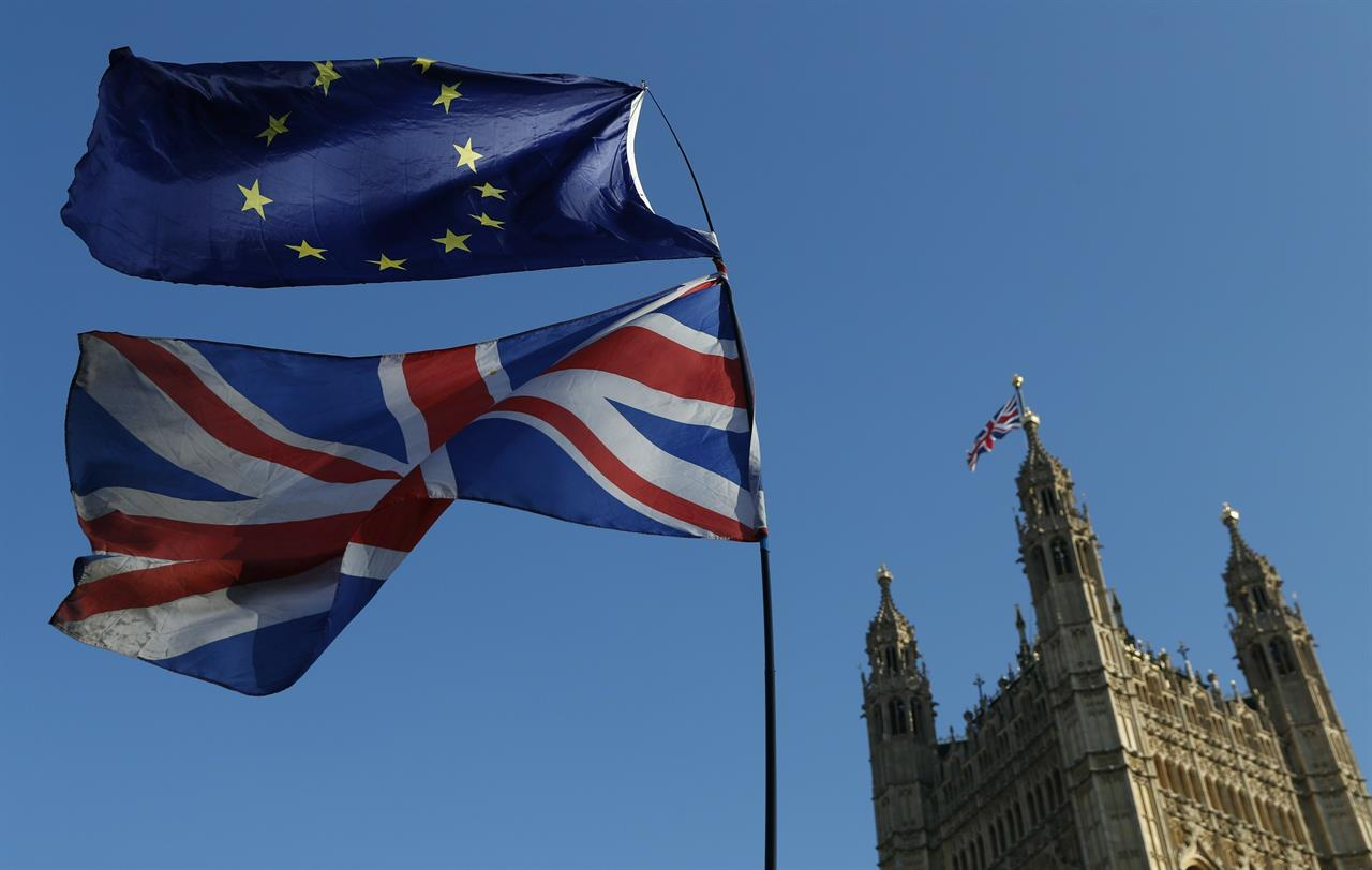 """FILE - In this Wednesday, Feb. 27, 2019 file photo the flag of the European Union and the British national flag are flown on poles during a demonstration by remain in the EU outside spporters the Palace of Westminster in London. It's more than four years since Britain voted to leave the European Union, and almost a year since Prime Minister Boris Johnson won an election by vowing to """"get Brexit done."""" Spoiler alert: It is not done. As negotiators from the two sides hunker down for their final weeks of talks on an elusive trade agreement, Britain and the EU still don't know whether they will begin 2021 with an organized partnership or a messy rivalry.  (AP Photo/Alastair Grant, File)"""