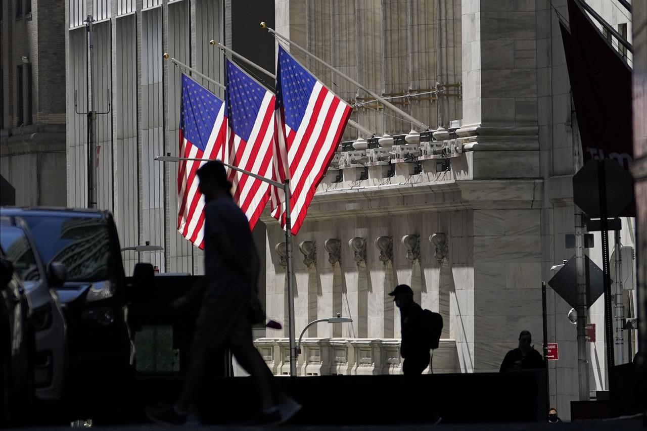 FILE - In this Oct. 14, 2020 file photo, pedestrians pass the New York Stock Exchange.  Stocks are mixed on Wall Street, following gains in European markets, as more U.S. companies report encouraging results for the summer earnings period. (AP Photo/Frank Franklin II)