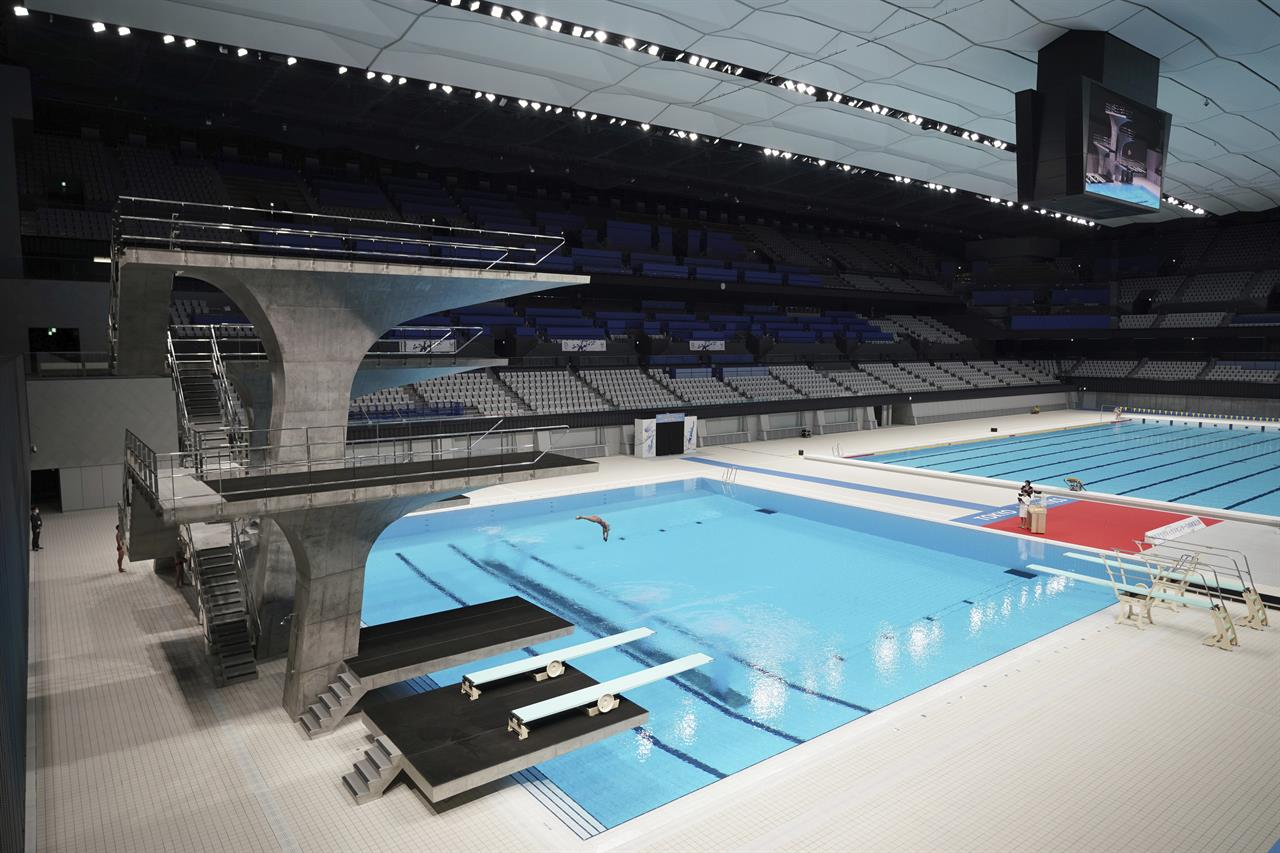 A diver demonstrates during a grand opening ceremony of Tokyo Aquatics Center Saturday, Oct. 24, 2020, in Tokyo. The Tokyo 2020 organizing committee held the grand opening ceremony Saturday at the aquatics center, planned to host Olympic artistic swimming, diving and swimming and Paralympics swimming events in 2021. (AP Photo/Eugene Hoshiko)
