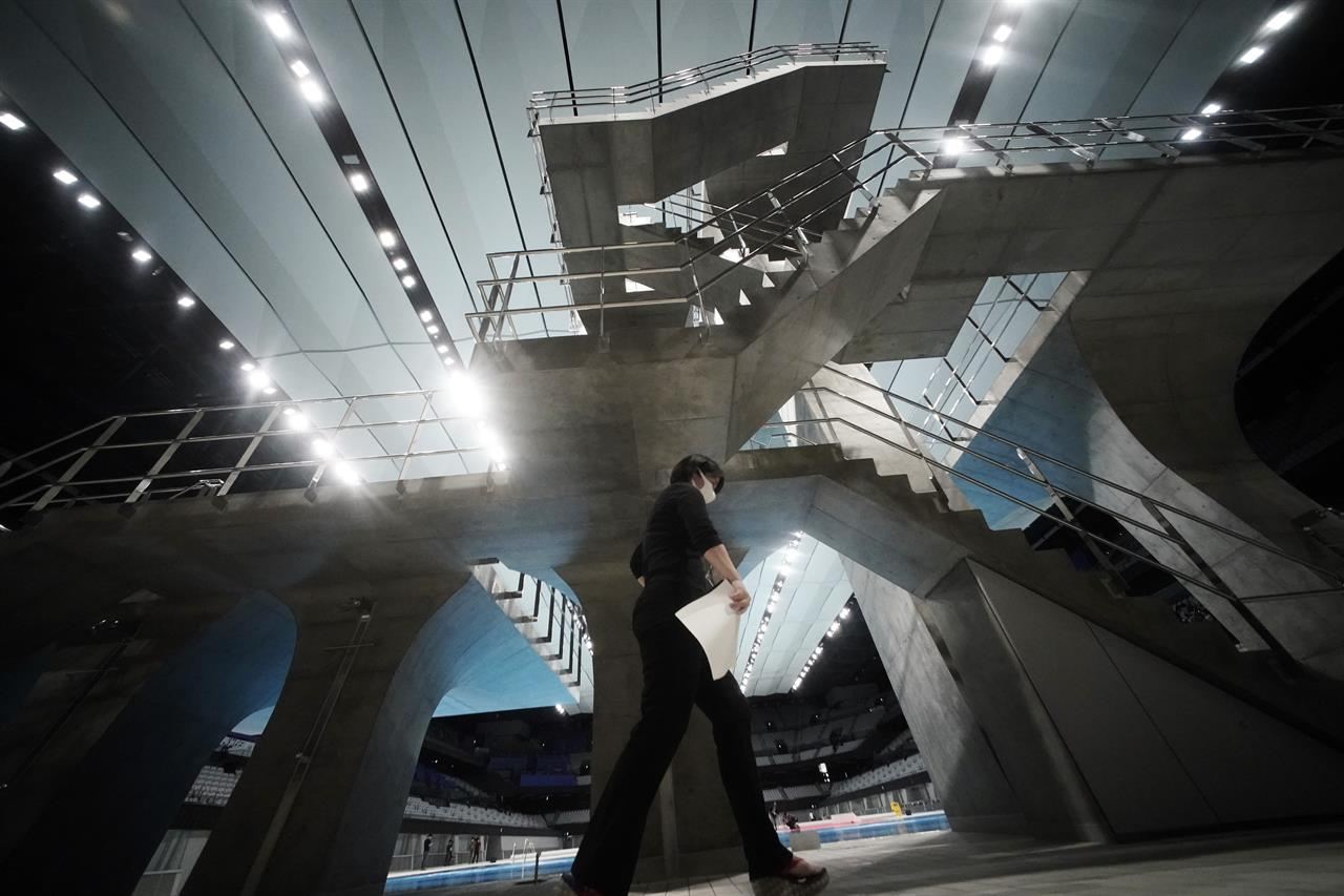 A woman walks by the diving platform at Tokyo Aquatics Center after its grand opening ceremony Saturday, Oct. 24, 2020, in Tokyo. The Tokyo 2020 organizing committee held the grand opening ceremony Saturday at the aquatics center, planned to host Olympic artistic swimming, diving and swimming and Paralympics swimming events in 2021. (AP Photo/Eugene Hoshiko)