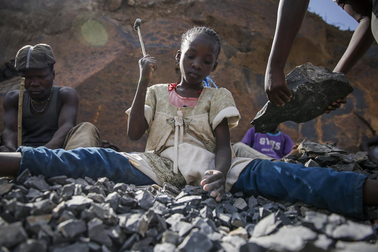 Irene Wanzila, 10, works breaking rocks with a hammer at the Kayole quarry in Nairobi, Kenya Tuesday, Sept. 29, 2020, along with her younger brother, older sister and mother, who says she was left without a choice after she lost her cleaning job at a private school when coronavirus pandemic restrictions were imposed. The United Nations says the COVID-19 pandemic risks significantly reducing gains made in the fight against child labor, putting millions of children at risk of being forced into exploitative and hazardous jobs, and school closures could exacerbate the problem. (AP Photo/Brian Inganga)