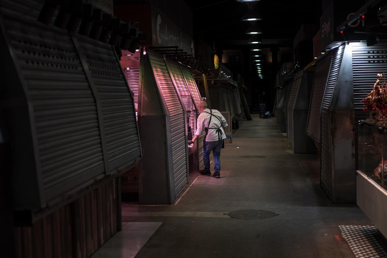 A vendor closes his cured ham shop in a market in Barcelona, Spain, Friday, Oct. 23, 2020. (AP Photo/Emilio Morenatti)