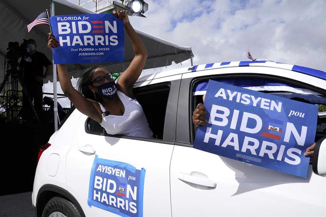 Nashley Harrigan, who is of Haitian descent, cheers from her vehicle at a car rally before a speech by former President Barack Obama who is campaigning for Democratic presidential candidate former Vice President Joe Biden at Florida International University, Saturday, Oct. 24, 2020, in North Miami, Fla. (AP Photo/Lynne Sladky)