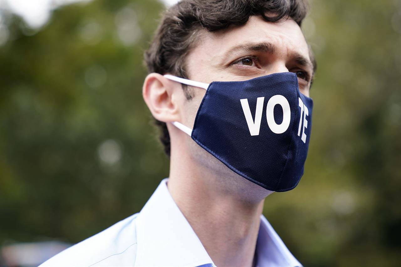 "Democratic candidate for Senate Jon Ossoff watches during a ""Get Out the Early Vote"" event at the SluttyVegan ATL restaurant on Tuesday, Oct. 27, 2020, in Jonesboro, Ga. (AP Photo/Brynn Anderson)"