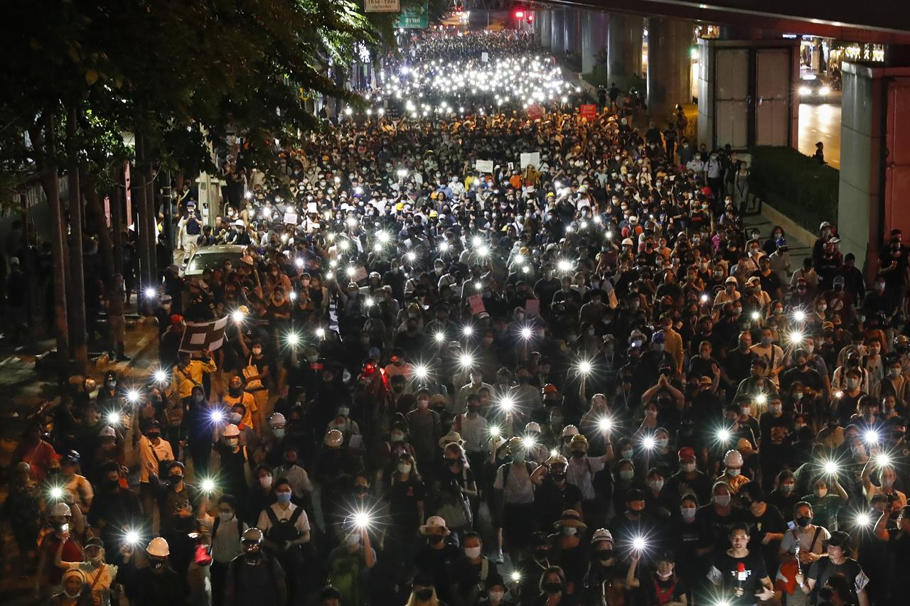Pro-democracy demonstrators shine their mobile phone lights as they march to the German Embassy in central Bangkok, Thailand, Monday, Oct. 26, 2020. As lawmakers debated in a special session in Parliament that was called to address political tensions, student-led rallies were set to continue with a march through central Bangkok on Monday evening to the German Embassy, apparently to bring attention to the time King Maha Vajiralongkorn spends in Germany. (AP Photo/Gemunu Amarasinghe)