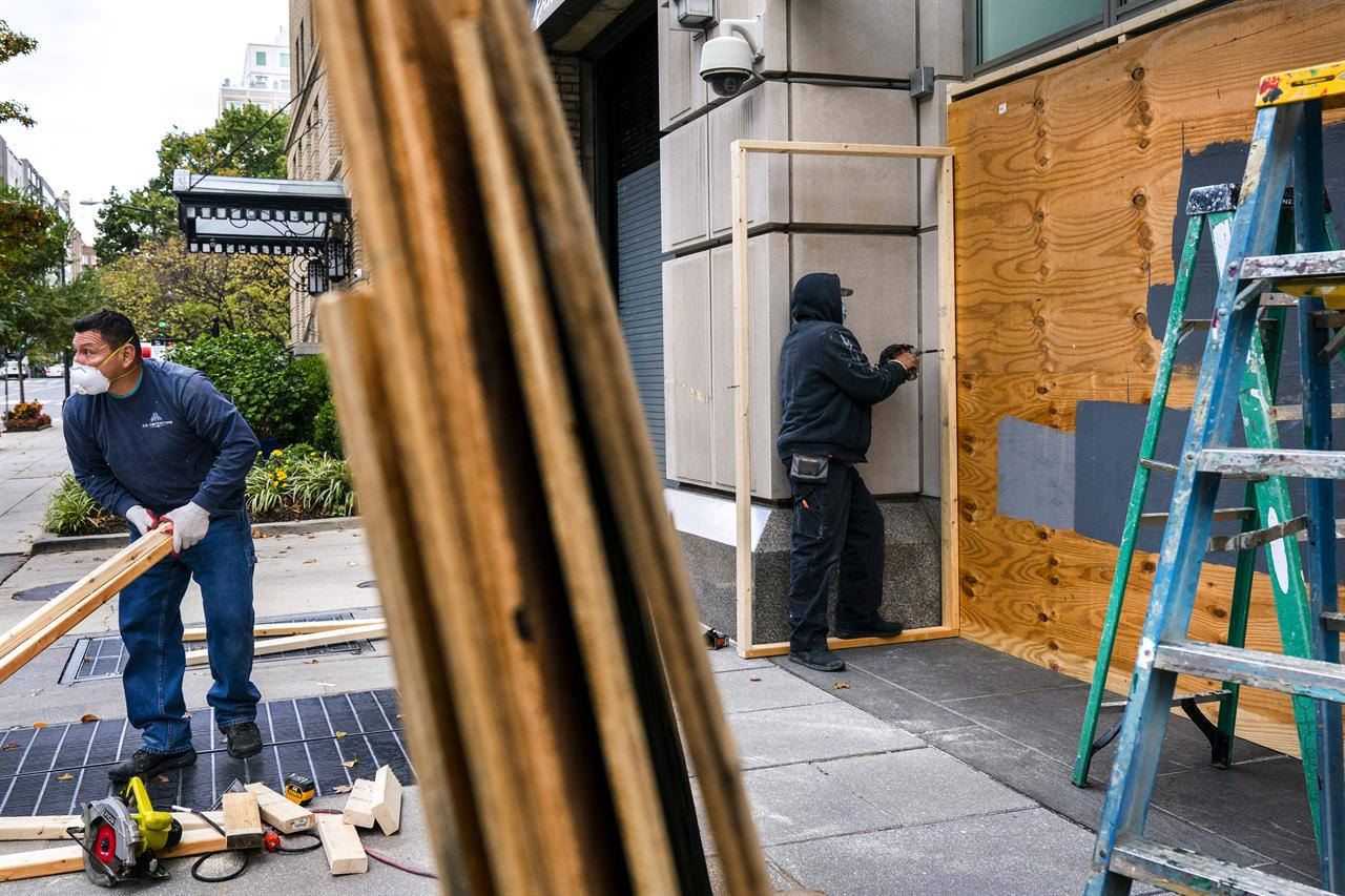 Ahead of the presidential election, workers board up Brown Bag, a restaurant on I Street NW, Friday, Oct. 30, 2020, near the White House in downtown Washington. (AP Photo/Jacquelyn Martin)
