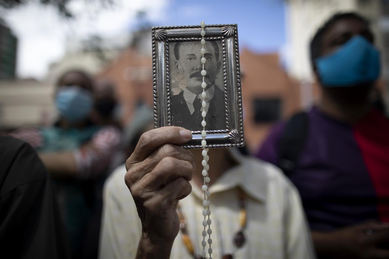 """A devotee holds up a framed image of the late Dr. Jose Gregorio Hernandez outside La Candelaria church where his remains are interred, in Caracas, Venezuela, Monday, Oct. 26, 2020. The remains of Hernandez, popularly known as the """"doctor of the poor"""", were exhumed on Monday in a closed ceremony in a church in downtown Caracas as part of the Vatican's demands for the beatification of the first Venezuelan layman. (AP Photo/Ariana Cubillos)"""