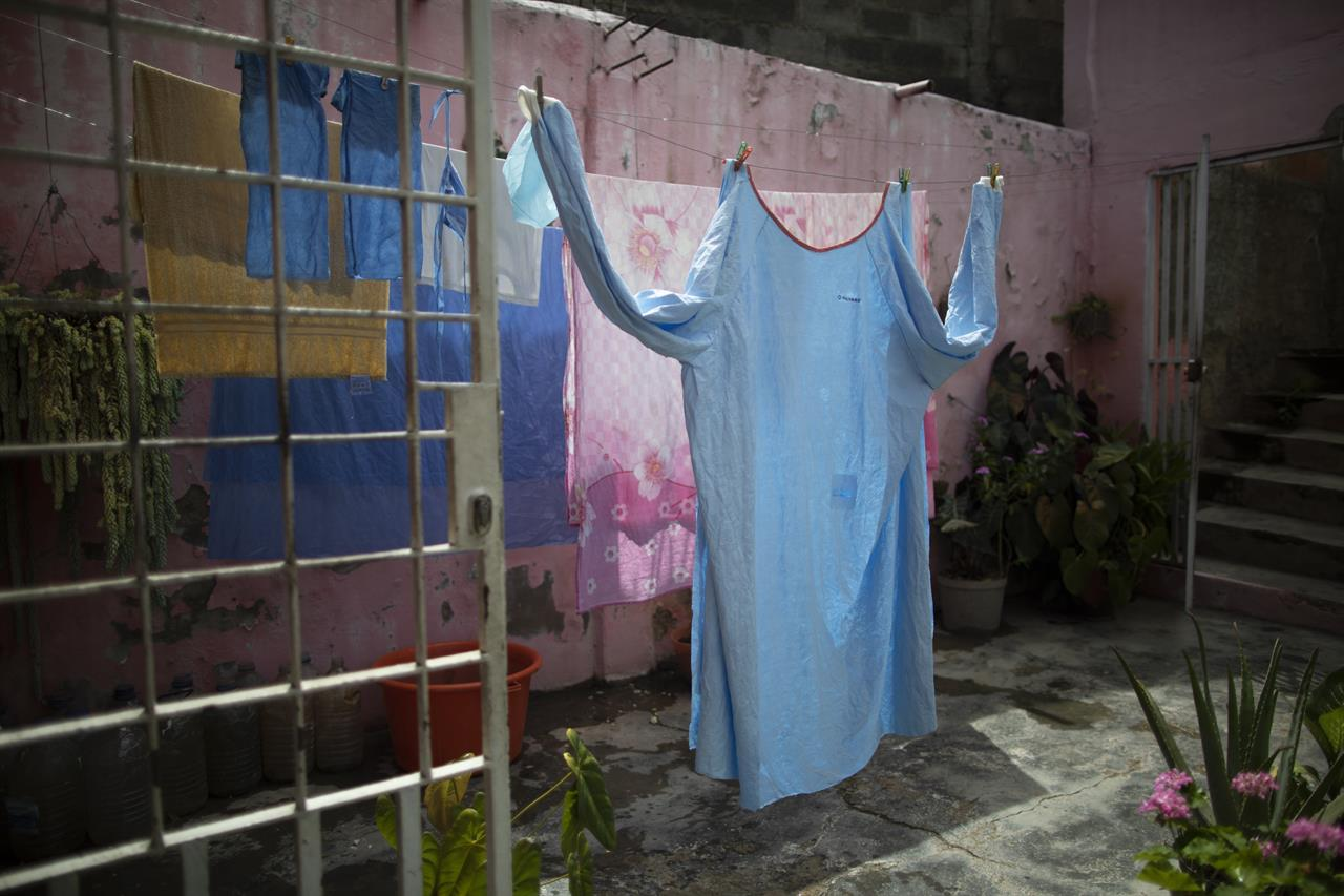 One of Elena's Suazo's two medical gowns hangs to dry at her parents' home in the Catia neighborhood of Caracas, Venezuela, Tuesday, Sept. 29, 2020, in between her twice-daily trips to care for her hospitalized father in the COVID-19 wing of the Jose Gregorio Hernandez public hospital. On a cafeteria worker's monthly salary, Suazo had no money to buy the needed protective gear, so her younger brother bought her one suit and her son's mother-in-law gave her a second, allowing her to attend him inside the hospital twice a day. (AP Photo/Ariana Cubillos)