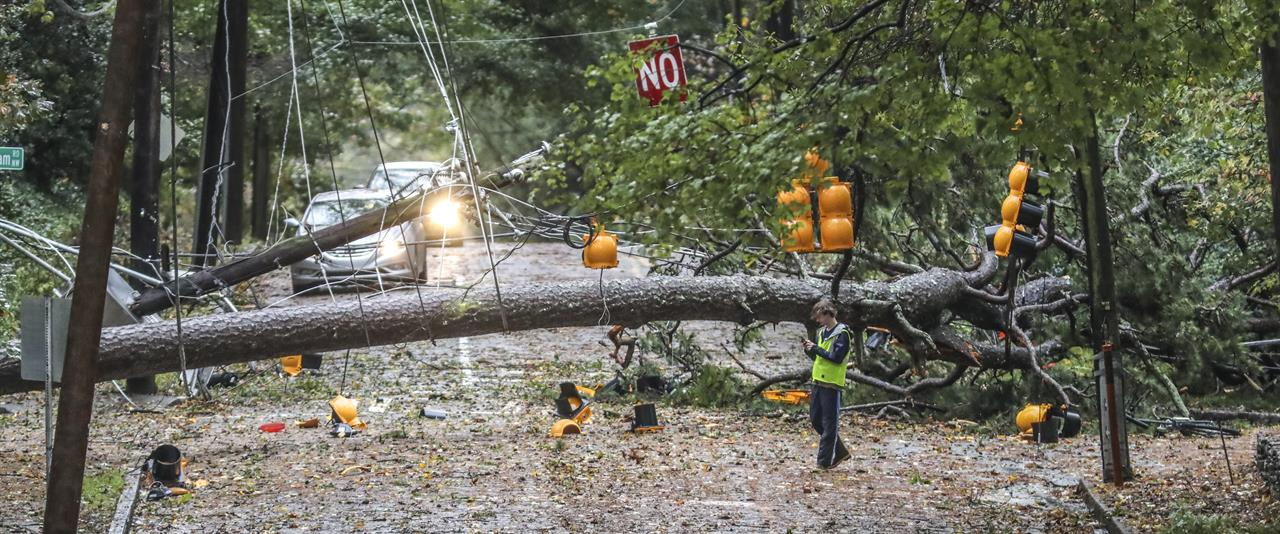 A large tree fell across West Wesley Road and Habersham Road where it remained closed most of the day Thursday, Oct. 29, 2020 in Atlanta. Rain bands and damaging winds from Tropical Storm Zeta swept through North Georgia on Thursday morning, leaving nearly 1 million in the dark. (John Spink/Atlanta Journal-Constitution via AP)